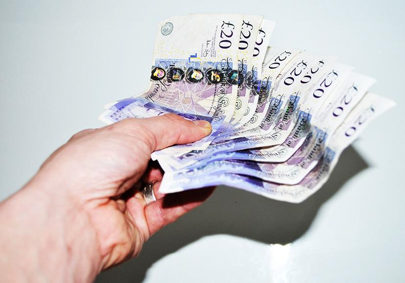 hand with twenty pound notes