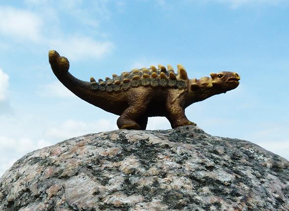 dinosaur on rock against the sky