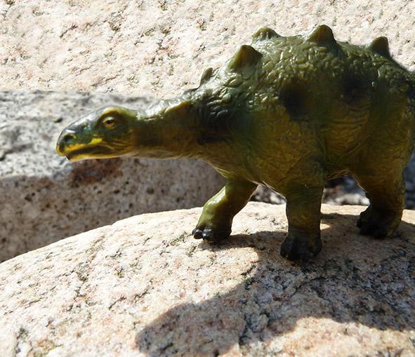 green dinosaur climbing cliffs