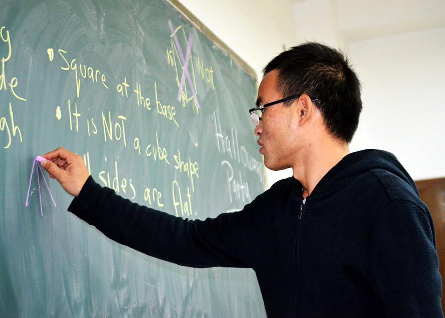 student writing math formula on black board