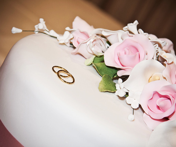 wedding cake decorated with rings and flowers